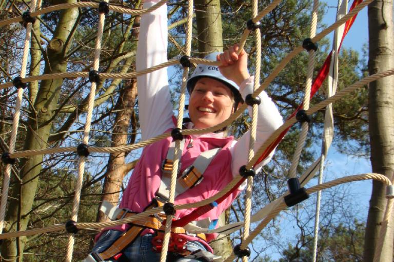 kletternde Frau im Kletterwald BinzProra